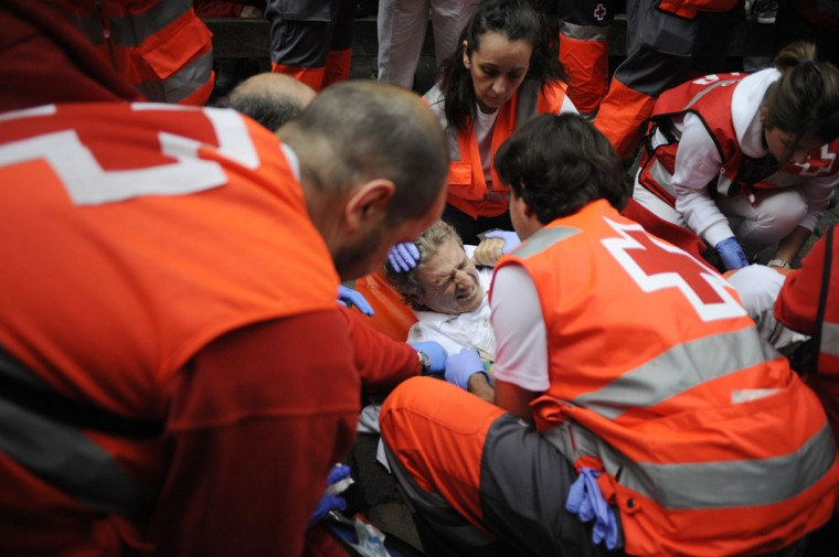Paramedics help an injured man during the first bull-run of the San Fermin Festival, on July 7, 2014, in Pamplona, northern Spain. (ANDER GILLENEA/AFP/Getty Images)