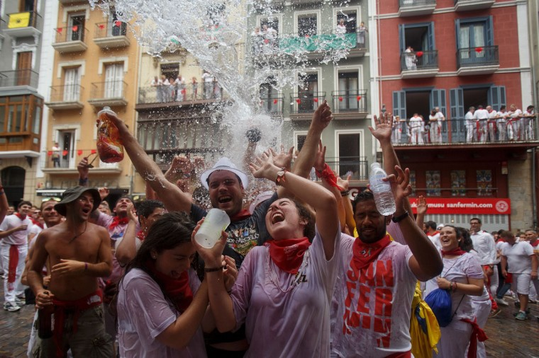 Revellers are soaked in water and wine thrown from balconies during the opening and the firing of the 'Chupinazo' rocket, which starts the 2014 Festival of the San Fermin Running of the Bulls on July 6, 2014 in Pamplona, Spain. (Photo by Pablo Blazquez Dominguez/Getty Images)