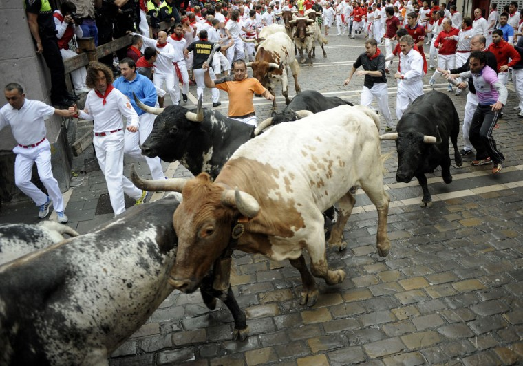 Participants run in front of Torrestrella's bulls during the first bull-run of the San Fermin Festival, on July 7, 2014, in Pamplona, northern Spain. (ANDER GILLENEA/AFP/Getty Images)