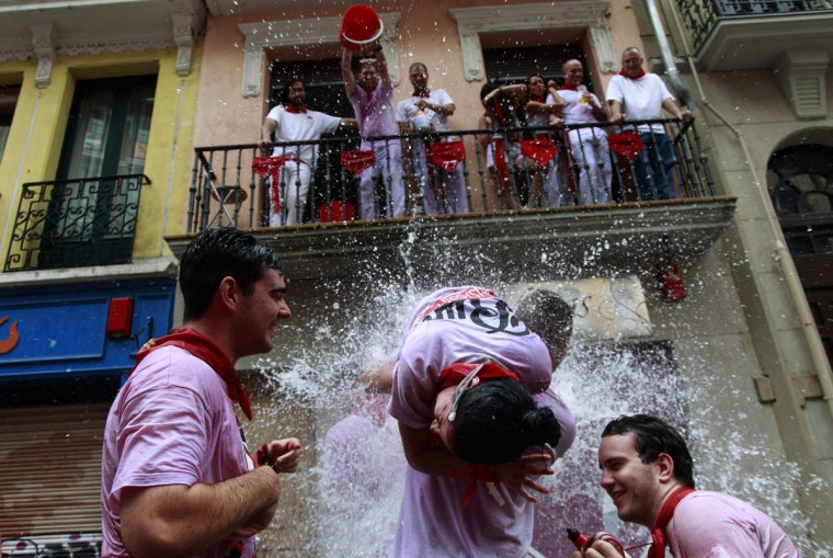 Revellers are drenched with water thrown from a balcony following the midday Chupinazo rocket announcing the start of the San Fermin festival in Pamplona on July 6, 2014. (REUTERS/JOSEBA ETXABURU)