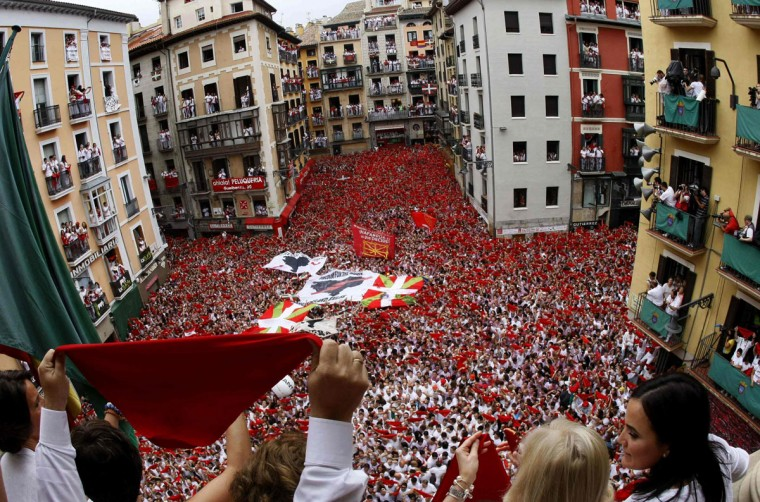 People cheer after hearing the midday Chupinazo rocket announcing the start of the San Fermin festival in Pamplona on July 6, 2014. (REUTERS/Stringer)