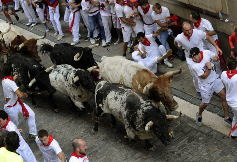 Runners sprint with Torrestrella fighting bulls on Santo Domingo street during the first running of the bulls of the San Fermin festival in Pamplona on July 7, 2014. (REUTERS/Eloy Alonso)
