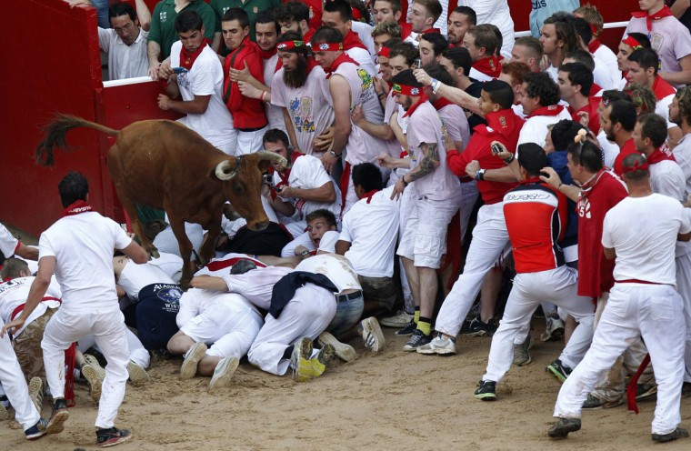 A fighting cow leaps over festival goers as she enters the ring following the first running of the bulls at the San Fermin festival in Pamplona on July 7, 2014. (REUTERS/Joseba Etxaburu)