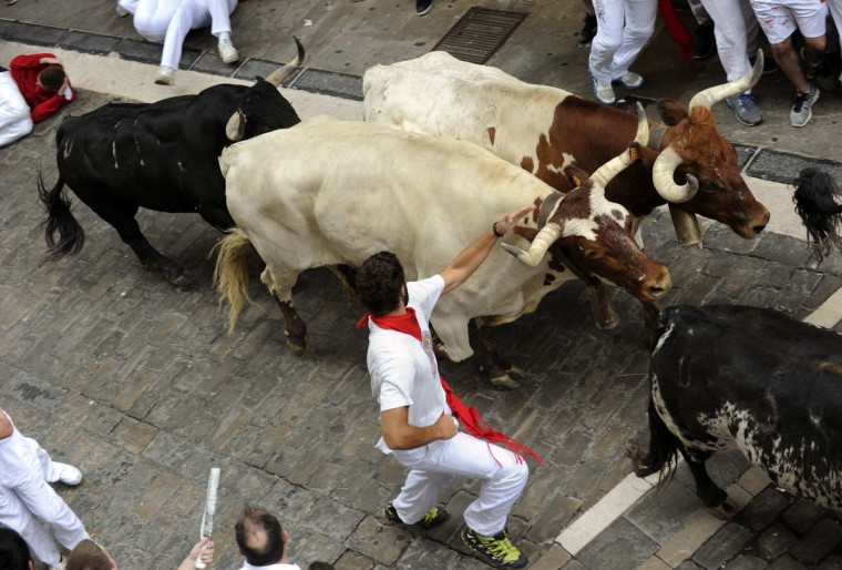 Runners sprint in front of Torrestrella fighting bulls on Santo Domingo street during the first running of the bulls of the San Fermin festival in Pamplona on July 7, 2014. (REUTERS/Eloy Alonso)