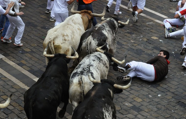 A runner falls in front of Torrestrella fighting bulls on Santo Domingo street during the first running of the bulls of the San Fermin festival in Pamplona on July 7, 2014. Four people were hospitalized on the first day of Spain's San Fermin bull run, a daily race through the narrow, cobbled streets of Pamplona that forms part of the northern city's week-long festival. (REUTERS/Eloy Alonso)