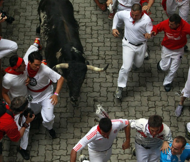 A runner tries to evade the horn of a Torrestrella fighting bull at the entrance to the bullring during the first running of the bulls of the San Fermin festival in Pamplona on July 7, 2014. Four people were hospitalized on the first day of Spain's San Fermin bull run, a daily race through the narrow, cobbled streets of Pamplona that forms part of the northern city's week-long festival. One runner was gored in the thigh while the other three suffered fractures during the race against five bulls which lasted 2 minutes and 25 seconds, according to the Red Cross. (REUTERS/Joseba Etxaburu)