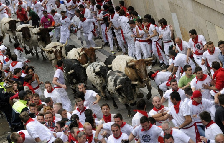 Runners sprint in front of Torrestrella fighting bulls on Santo Domingo street during the first running of the bulls of the San Fermin festival in Pamplona on July 7, 2014. Four people were hospitalized on the first day of Spain's San Fermin bull run, a daily race through the narrow, cobbled streets of Pamplona that forms part of the northern city's week-long festival. One runner was gored in the thigh while the other three suffered fractures during the race against five bulls which lasted 2 minutes and 25 seconds, according to the Red Cross. (REUTERS/Eloy Alonso)