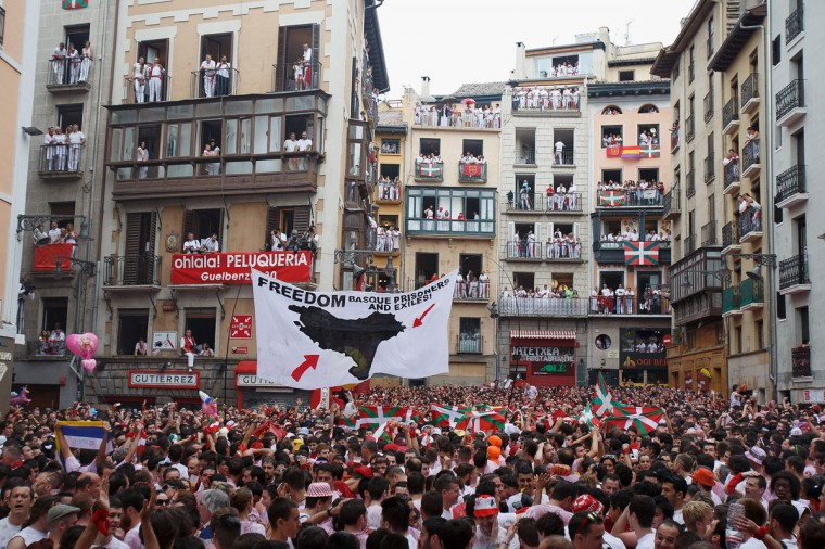 A protest banner reading 'Freedom Basque prisoners and exiles!' is lifted while thousands of revellers sing and dance during the opening and the firing of the 'Chupinazo' rocket, which starts the 2014 Festival of the San Fermin Running of the Bulls on July 6, 2014 in Pamplona, Spain. (Photo by Pablo Blazquez Dominguez/Getty Images)