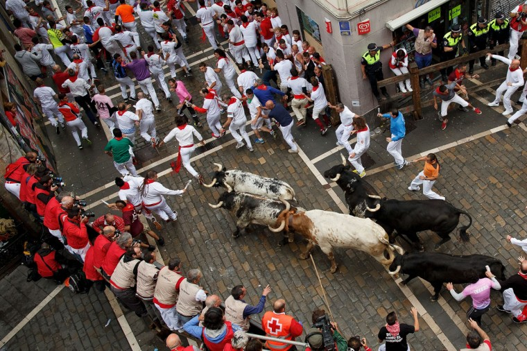 Revellers run with Torrestrella's fighting bulls along the Curva de Estafeta during the second day of the San Fermin Running Of The Bulls festival on July 7, 2014 in Pamplona, Spain. (Photo by Pablo Blazquez Dominguez/Getty Images)
