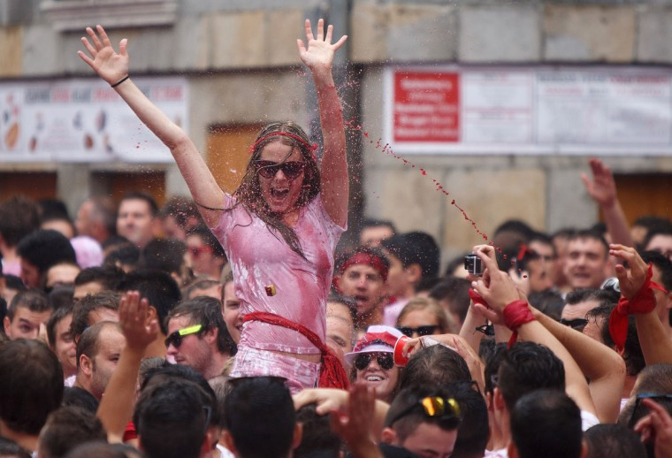 Revellers cheer and throw red wine during the opening and the firing of the 'Chupinazo' rocket, which starts the 2014 Festival of the San Fermin Running of the Bulls on July 6, 2014 in Pamplona, Spain. (Photo by Pablo Blazquez Dominguez/Getty Images)