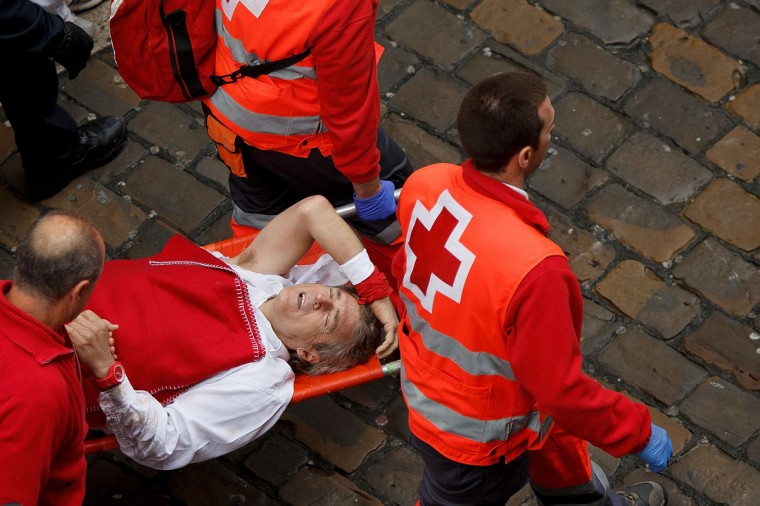 Medical services carry a runner after he was charged by the Torrestrella's fighting bulls along the Calle Estafeta during the second day of the San Fermin Running Of The Bulls festival on July 7, 2014 in Pamplona, Spain. (Photo by Pablo Blazquez Dominguez/Getty Images)
