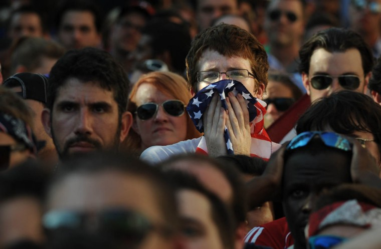 A fan holds the flag to his face as he watches the soccer game in overtime after Belgium scores a goal. Fans gather at the Power Plant Live! to watch the United States' World Cup Round of 16 match against Belgium. The US lost. (Algerina Perna/Baltimore Sun)