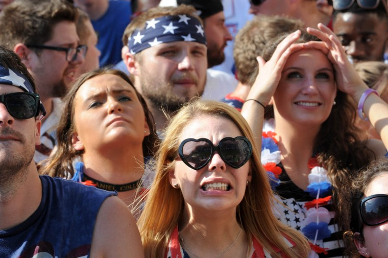 Caitlyn Kielb, 24, from Baltimore, center, grimaces during a play in the soccer match. Behind her at left is Samantha Chittim, 18, from Broadneck. Behind her right is Petra Brusnigham, 18, from Severna Park. Fans gather at the Power Plant Live! to watch the United States' World Cup Round of 16 match against Belgium. The US lost. (Algerina Perna/Baltimore Sun)