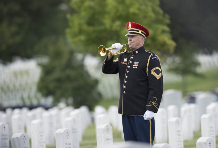 A bugler plays taps during funeral services for US Army Major General Harold Greene at Arlington National Cemetery in Arlington, Virginia, on August 14, 2014. Major General Greene was shot dead on August 5, 2014 at a training center in Kabul in an attack that left more than a dozen others wounded, including a senior German officer. He was the highest ranking US Army officer killed in combat since the Vietnam War. (Saul Loeb/Getty Images)