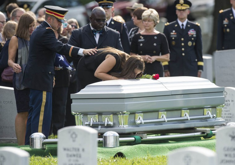 Amelia Greene kisses the casket of her father, US Army Major General Harold Greene, alongside Harold Greene's widow, Susan Myers (Left) and son First Lt. Matthew Greene (2nd from Left) during funeral services at Arlington National Cemetery in Arlington, Virginia, on August 14, 2014. Major General Harold J. Greene was shot dead on August 5, 2014 at a training center in Kabul in an attack that left more than a dozen others wounded, including a senior German officer. He was the highest ranking US Army officer killed in combat since the Vietnam War. (Saul Loeb/Getty Images)