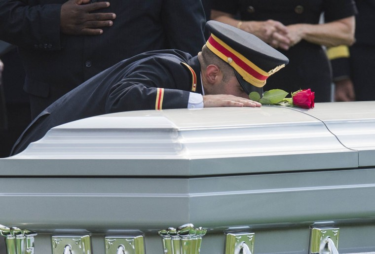 First Lt. Matthew Greene kneels down at the casket of his father, US Army Major General Harold Greene, during funeral services at Arlington National Cemetery in Arlington, Virginia, on August 14, 2014. Major General Greene was shot dead on August 5, 2014 at a training center in Kabul in an attack that left more than a dozen others wounded, including a senior German officer. He was the highest ranking US Army officer killed in combat since the Vietnam War. (Saul Loeb/Getty Images)
