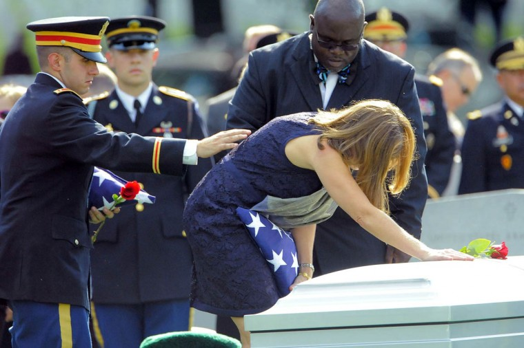 Dr. Susan Myers places a rose on the casket of her husband, Major General Harold J. Greene of the U.S. Army as her son, 1st Lt. Matthew Greene consoles her during Greene's burial at Arlington National Cemetery in Arlington, Va. on Thursday, August 14, 2014. (Al Drago/Baltimore Sun)