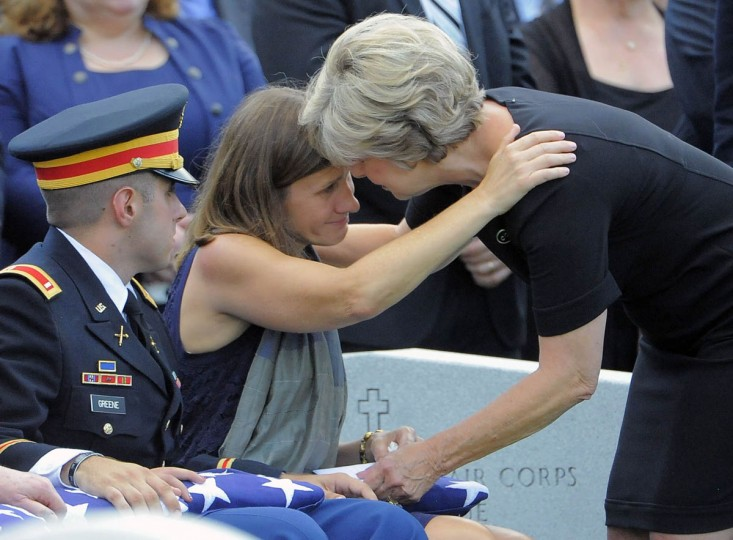 Widow Dr. Susan Myers receives a hug from Army Arlington Lady Lynda Flowers after being presented a flag during the burial of US Army Major General Harold Greene at Arlington National Cemetery in Arlington, Virginia, on August 14, 2014. Greene was the highest ranking US Army officer killed in combat since the Vietnam War. (Al Drago/Baltimore Sun)