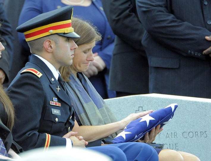 Dr. Susan Myers looks at the flag that covered the casket of her husband, Major General Harold J. Greene of the U.S. Army, as she sits alongside her son, 1st Lt. Matthew Greene, during Greene's burial at Arlington National Cemetery in Arlington, Va. on Thursday, August 14, 2014. (Al Drago/Baltimore Sun)