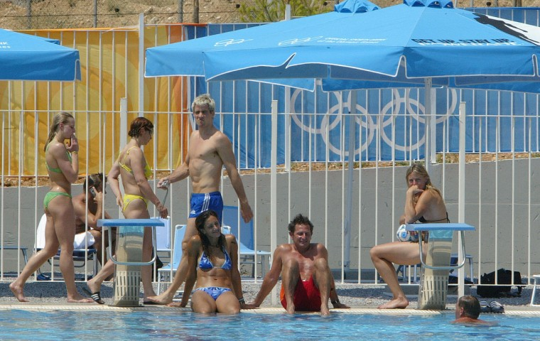 Athletes and delegation members relax by the pool at the Olympic village in Athens 10 August 2004. (Javier Soriano/Getty Images)