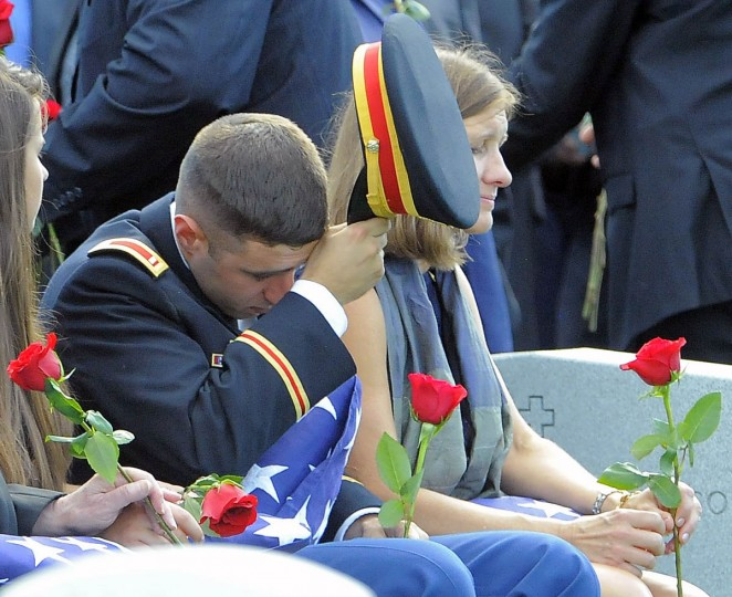 1st Lt. Matthew Greene wipes his brow alongside his mother, Dr. Susan Myers, after receiving a rose to place on the casket of his father, Major General Harold J. Greene of the U.S. Army during his burial at Arlington National Cemetery in Arlington, Va. on Thursday, August 14, 2014. (Al Drago/Baltimore Sun)