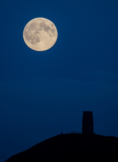 The moon rises above Glastonbury Tor on August 10, 2014 in Somerset, England. Tonight's supermoon, or perigee moon referring to its closest point to earth, is the second one of the summer. According to NASA, the moon appears 30 percent brighter and 14 percent bigger than normal. Another supermoon will appear September 9. (Matt Cardy/Getty Images)
