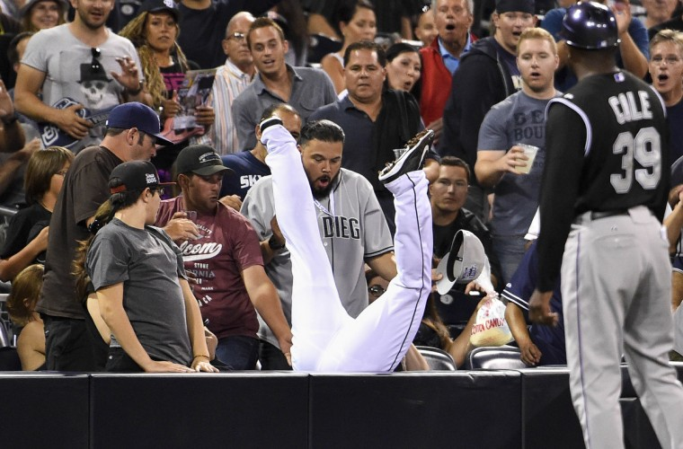 Chris Nelson #1 of the San Diego Padres flips into the stands as he makes the catch on a foul ball hit by Charlie Blackmon #19 of the Colorado Rockies during the eighth inning of a baseball game at Petco Park in San Diego, California. (Denis Poroy/Getty Images)