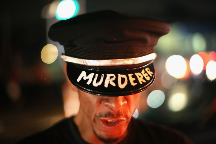Demonstrators gather along West Florissant Avenue to protest the shooting and death of Michael Brown on August 15, 2014 in Ferguson, Missouri. Brown was shot and killed by a Ferguson police officer on August 9. Tonight's demonstration again ended with protestors clashing with police followed by more looting. (Photo by Scott Olson/Getty Images)