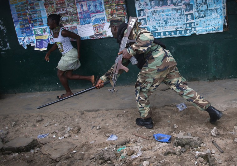 A Liberian Army soldier, part of the Ebola Task Force, beats a local resident while enforcing a quarantine on the West Point slum in Monrovia, Liberia. The government ordered the quarantine of West Point, a congested seaside slum of 75,000, on Wednesday, in an effort to stop the spread of the virus in the capital city. Liberian soldiers were also sent in to the seaside favela to extract West Point Commissioner Miata Flowers and her family members after residents blamed the government for setting up a holding center for suspected Ebola patients to be set up in their community. A mob overran and closed the facility on August 16. The military also began enforcing a quarantine on West Point, a congested slum of 75,000, fearing a spread of the epidemic. The Ebola virus has killed more than 1,200 people in four African nations, more in Liberia than any other country. (John Moore/Getty Images)