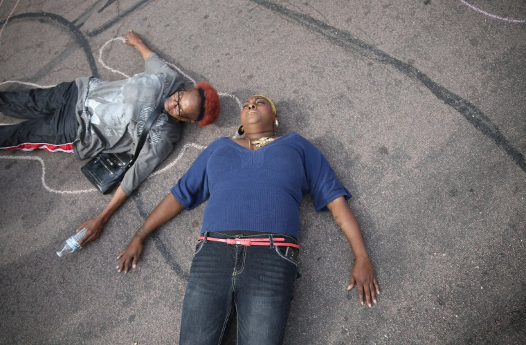 Protesters lay on the ground to draw lines around their bodies as they and other demonstrators protest outside of the Buzz Westfall Justice Center where a grand jury will begin looking at the circumstances surrounding the fatal police shooting of an unarmed teenager Michael Brown in Clayton, Missouri. Brown was shot and killed by a Ferguson, Missouri police officer on August 9. Despite the Brown family's continued call for peaceful demonstrations, violent protests have erupted nearly every night in Ferguson since his death. (Joe Raedle/Getty Images)