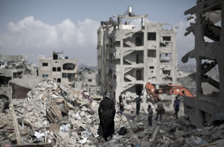 A Palestinian woman walks through the rubble of destroyed buildings in part of Gaza City's al-Tufah neighborhood as the fragile ceasefire in the Gaza Strip entered a second day on August 6, 2014 while Israeli and Palestinian delegations prepared for crunch talks in Cairo to try to extend the 72-hour truce. The ceasefire, which came into effect on August 5, has brought relief to both sides after one month of fighting killed 1,875 Palestinians and 67 people on the Israeli side. (Mahmud Hams/Getty Images)