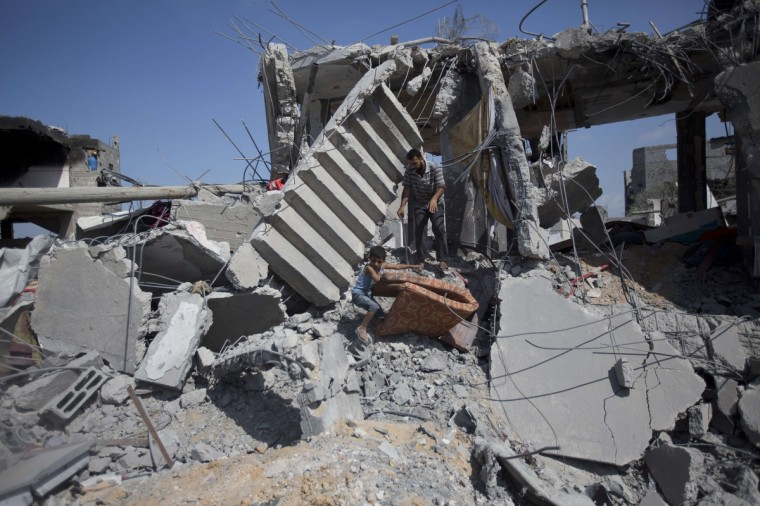 Palestinians salvage items from the rubble of destroyed buildings in part of Gaza City's al-Tufah neighborhood as the fragile ceasefire in the Gaza Strip entered a second day on August 6, 2014 while Israeli and Palestinian delegations prepared for crunch talks in Cairo to try to extend the 72-hour truce. The ceasefire, which came into effect on August 5, has brought relief to both sides after one month of fighting killed 1,875 Palestinians and 67 people on the Israeli side. (Mahmud Hams/Getty Images)