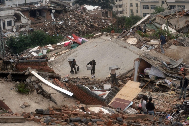 Local residents collect their belongings from the debris of their damaged houses in Ludian county in Zhaotong, southwest China's Yunnan province. The death toll from an earthquake that devastated a remote region of China jumped to nearly 600 people, authorities said, as volunteer rescuers were warned away. (Getty Images)