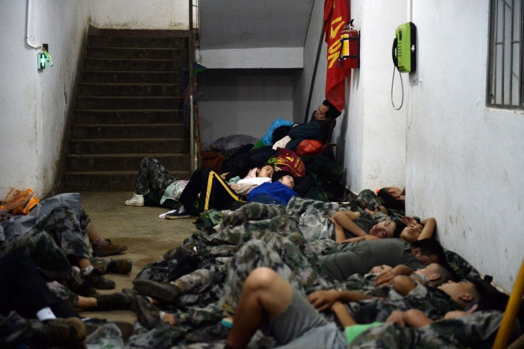 Rescuers sleep on the ground in Ludian county in Zhaotong, southwest China's Yunnan province. The death toll from an earthquake that devastated a remote region of China jumped to nearly 600 people, authorities said, as volunteer rescuers were warned away. (Getty Images)
