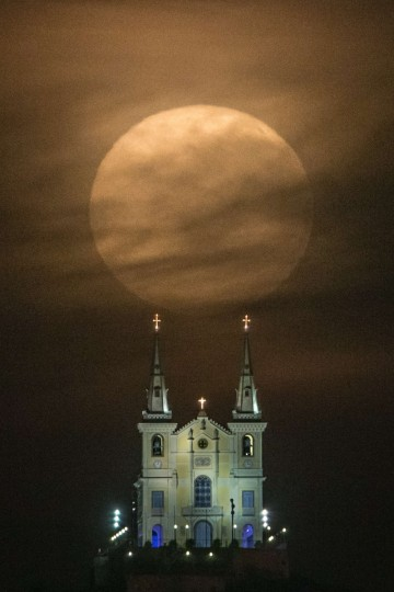 The full moon descends behind the Nossa Senhora da Penha Church in Rio de Janeiro, Brazil, on August 10, 2014. In this time of the year the orb is at the closest point to the earth. Experts name this phenomenon the supermoon or perigee. (Yasuyoshi Chiba/Getty Images)