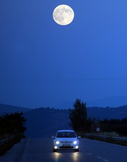 "The full moon, nicknamed ""the supermoon"", rises over road near the town of Bitola on August 10, 2014. A supermoon is the coincidence of a full moon or a new moon with the closest approach the Moon makes to the Earth on its elliptical orbit, resulting in the largest apparent size of the lunar disk as seen from Earth. (Robert Atanasovski/Getty Images)"
