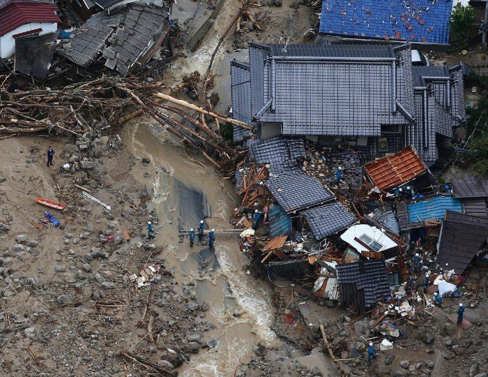 This aerial view shows rescue workers looking for survivors at the site of a landslide after heavy rains hit the city of Hiroshima, western Japan. The number of people known to have died when a hillside collapsed in western Japan has hit 27, the government said on August 20, with a further 10 people still unaccounted for. (Jiji Press/Getty Images)