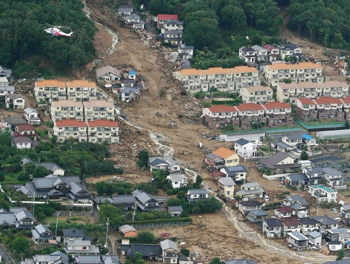 This aerial view shows the damage caused by a landslide after heavy rains hit the city of Hiroshima, western Japan. At least 18 people were killed and another 13 were still missing after a huge landslide engulfed homes in western Japan, reports said on August 20. (Jiji Press/Getty Images)