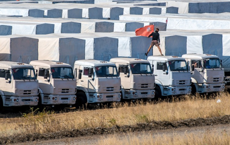 A driver installs a red flag on his lorry, parked with other lorries of the Russian humanitarian convoy not far from a checkpoint at the Ukrainian border some 30 km outside the town of Kamensk-Shakhtinsky in the Rostov region. A tension between Moscow and Kiev simmering over Russia's decision to try and deliver what it claims to be a huge humanitarian aid convoy that the Ukrainian authorities fear may be used to smuggle in arms to the pro-Kremlin insurgents. (Dmitry Serebrayakov/Getty Images)