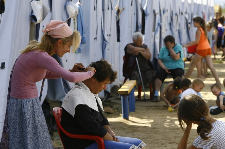 A refugee from eastern Ukraine cuts her counterpart's hair in a refugee camp near the Russian city of Donets'k, Rostov region, about 15 kilometres from the Russian-Ukrainian border. Some 285,000 people have already fled their homes due to the conflict in east Ukraine, it is estimated, with many leaving for other parts of the country, but close to 168,000 seeking sanctuary in Russia. (Sergei Venyavsky/Getty Images)