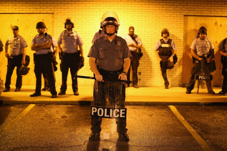 Police stand guard before the mandatory midnight curfew on August 16, 2014 in Ferguson, Missouri. The curfew was imposed on Saturday in an attempt to reign in the violence that has erupted nearly every night in the suburban St. Louis town since the shooting death of teenager Michael Brown by a Ferguson police officer on August 9. (Scott Olson/Getty Images)