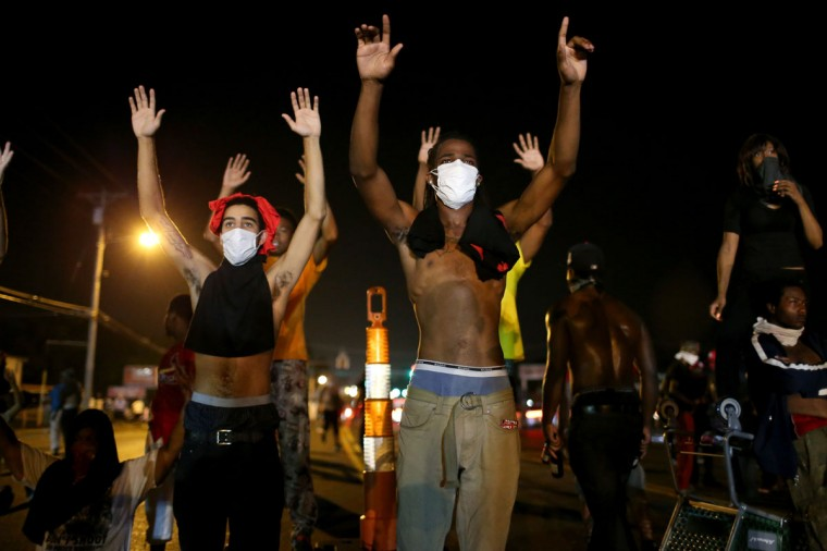 "Demonstrators raise their arms and chant, ""Hands up, Don't Shoot"", as police clear them from the street as they protest the shooting death of Michael Brown on August 17, 2014 in Ferguson, Missouri. Police sprayed pepper spray, shot smoke, gas and flash grenades as violent outbreaks have taken place in Ferguson since the shooting death of Michael Brown by a Ferguson police officer on August 9th. (Joe Raedle/Getty Images)"