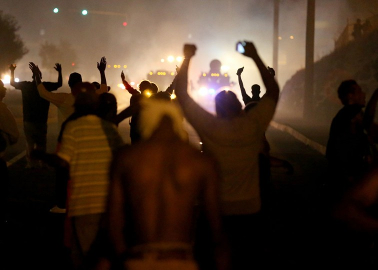 Demonstrators hold up their hands as police fire tear gas at them as they protest the shooting death of Michael Brown on August 17, 2014 in Ferguson, Missouri. Police sprayed pepper spray, shot smoke, gas and flash grenades as violent outbreaks have taken place in Ferguson since the shooting death of Michael Brown by a Ferguson police officer on August 9th. (Joe Raedle/Getty Images)