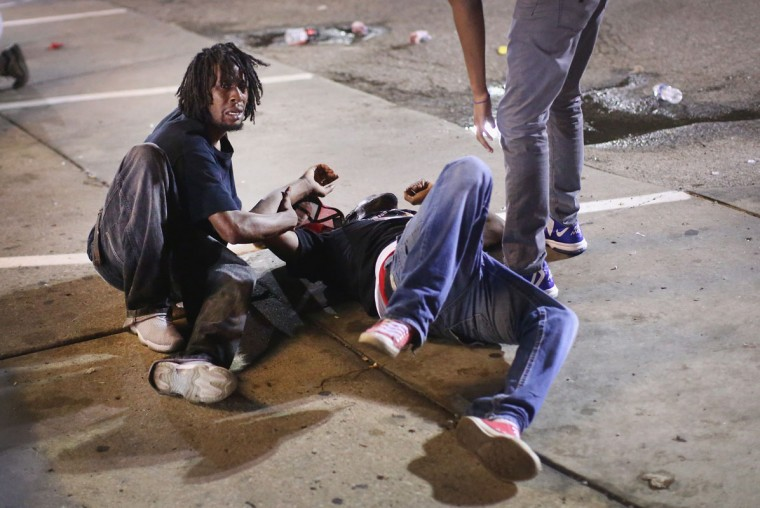A man gets help after being overcome by tear gas that police launched at demonstrators protesting the killing of teenager Michael Brown on August 17, 2014 in Ferguson, Missouri. Police shot smoke and tear gas into the crowd of several hundred as they advanced near the police command center which has been set up in a shopping mall parking lot. Brown was shot and killed by a Ferguson police officer on August 9. Despite the Brown family's continued call for peaceful demonstrations, violent protests have erupted nearly every night in Ferguson since his death. (Scott Olson/Getty Images)