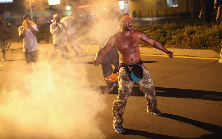 Demonstrators protesting the killing of teenager Michael Brown by a Ferguson police stand in a cloud of tear gas after the protest was attacked by police August 17, 2014 in Ferguson, Missouri. Despite the Brown family's continued call for peaceful demonstrations, violent protests have erupted nearly every night in Ferguson since his death. (Scott Olson/Getty Images)