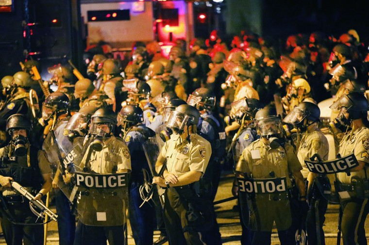 Police advance on demonstrators protesting the killing of teenager Michael Brown on August 17, 2014 in Ferguson, Missouri. Police shot smoke and tear gas into the crowd of several hundred as they advanced near the police command center which has been set up in a shopping mall parking lot. Brown was shot and killed by a Ferguson police officer on August 9. Despite the Brown family's continued call for peaceful demonstrations, violent protests have erupted nearly every night in Ferguson since his death. (Scott Olson/Getty Images)