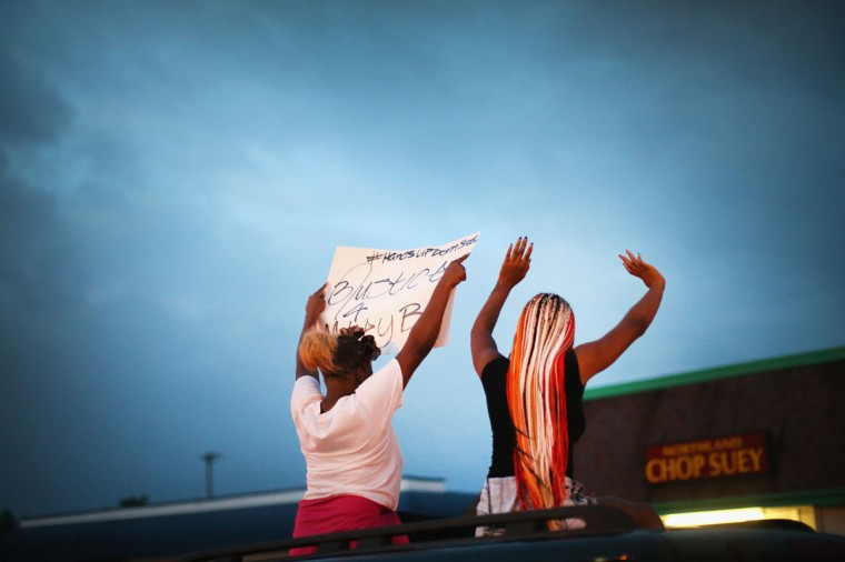 Demonstrators raise their arms during a protest against the killing of teenager Michael Brown on August 17, 2014 in Ferguson, Missouri. Despite the Brown family's continued call for peaceful demonstrations, violent protests have erupted nearly every night in Ferguson since his death. (Scott Olson/Getty Images)