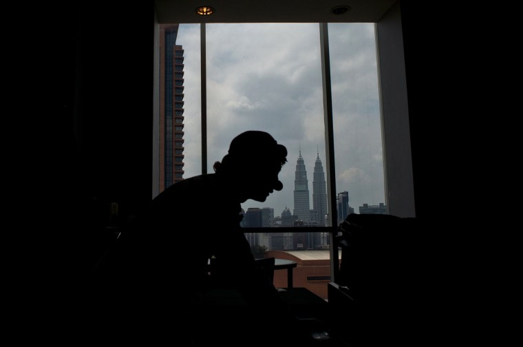 A clown is silhouetted against the backdrop of Malaysia's iconic Twin Towers during a Clown Festival in Kuala Lumpur on August 17, 2014. Around 80 clowns from all over Malaysia took part in the event organized by the Association of Clowns Malaysia to provide a platform for clown education, acquiring new skills and offering members support. (Manan Vatsyayana/AFP/Getty Images)