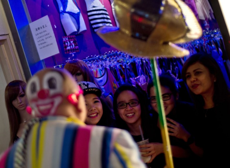 A clown entertains passersby as a group of the entertainers parade during the Clown Festival in Kuala Lumpur on August 17, 2014. Around 80 clowns from all over Malaysia took part in the event organized by the Association of Clowns Malaysia to provide a platform for clown education, acquiring new skills and offering members support. (Manan Vatsyayana/AFP/Getty Images)