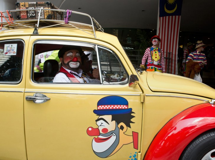 A Malaysian clown named Mr. Potato (C) drives his Beetle during the Clown Festival in Kuala Lumpur on August 17, 2014. Around 80 clowns from all over Malaysia took part in the event organized by the Association of Clowns Malaysia to provide a platform for clown education, acquiring new skills and offering members support. (Manan Vatsyayana/AFP/Getty Images)